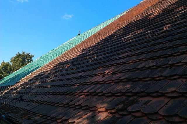 częściowo zafoliowany i rozebrany stary dach