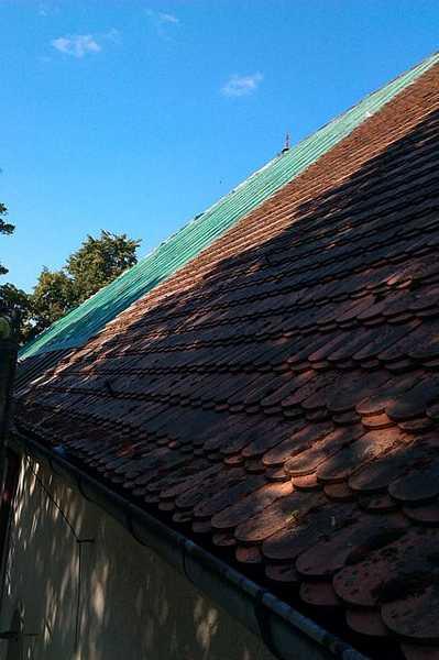 czeęściowo rozebrana stara karpiówka i zafoliowany odcinek dachu